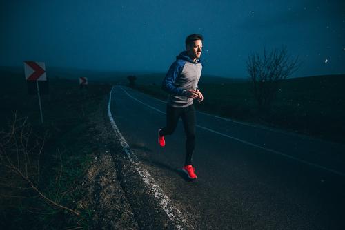 Man jogging at night on a rural road