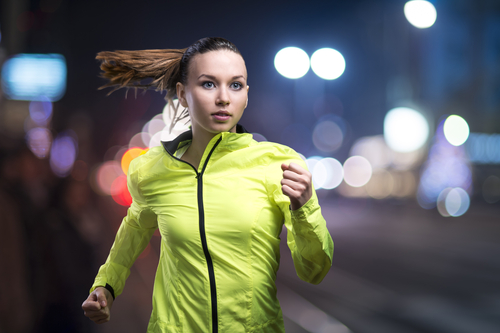 Woman jogging at night with bright clothes