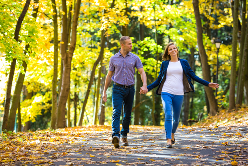 Couple walking in park with autumn leaves