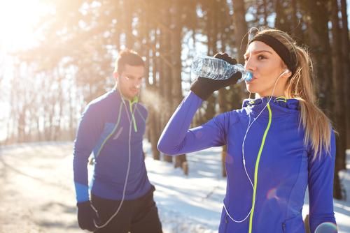 Winter walkers drinking a water bottle