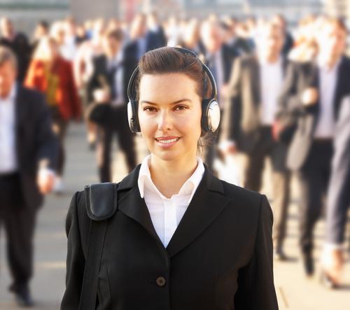 Businesswoman walking with headphones