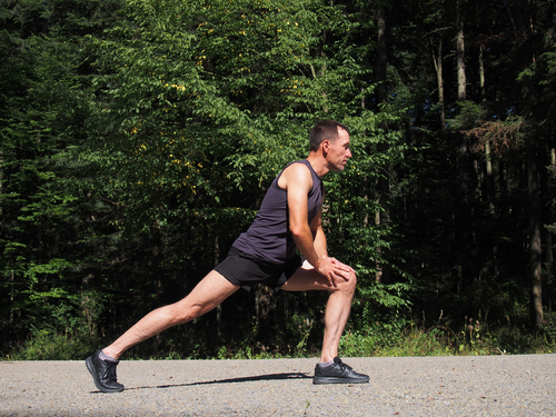 Man doing lunches to stretch after walking