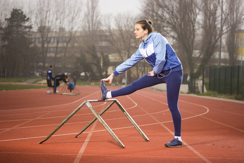 Woman stretching hamstrings on a running track