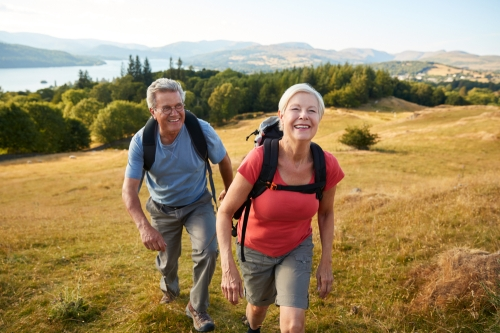 Senior couple hiking up a hill