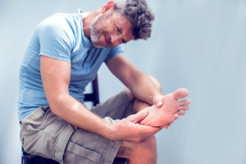 Man grimacing due to foot pain