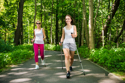 Women power walking with poles