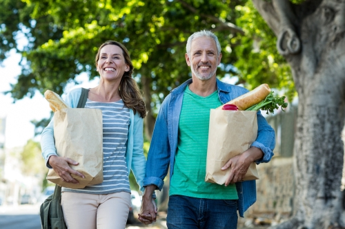 Senior couple walking with groceries