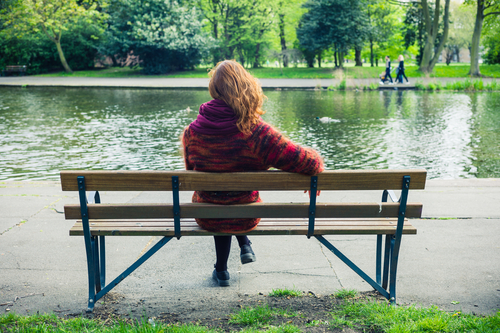 Woman sitting on park bench in front of lake