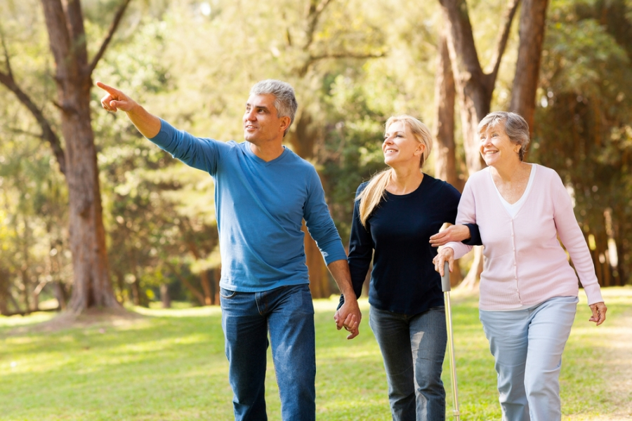 Couple and mom walking in park for fitness