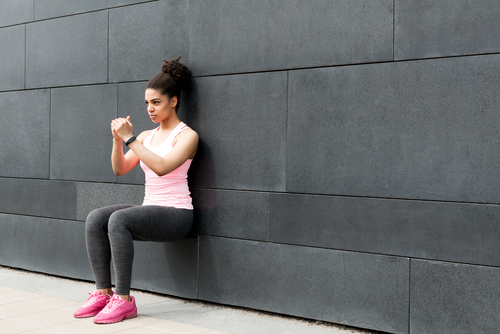 Woman doing a wall sit exercise