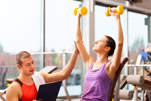 Trainer helping woman lift weights