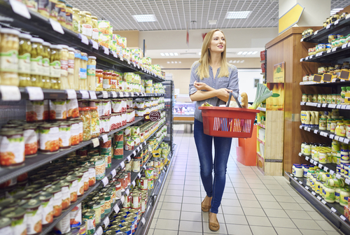 woman walking supermarket aisle with basket
