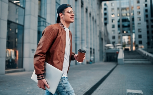Young man with computer crossing the street