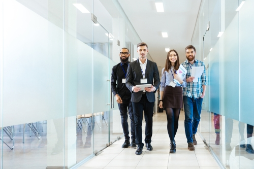 Diverse team of young businesspeople walking