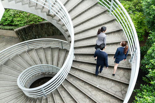 businesspeople walking up a spiral staircase