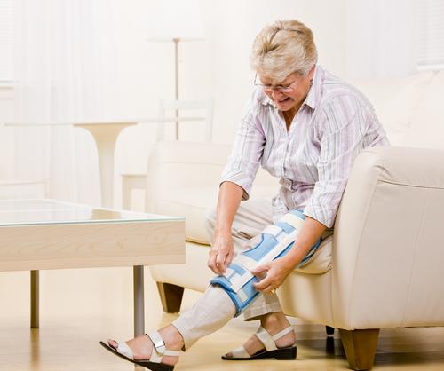 Older woman adjusting knee brace