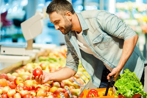 Man choosing an apple - health food concept
