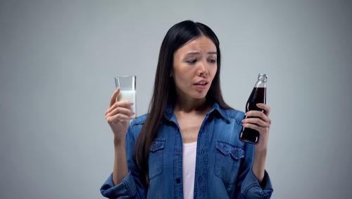 Woman choosing between soda and milk