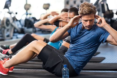 Man doing crunches in gym class