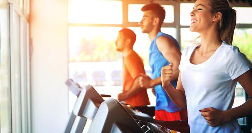 Woman and 2 men running on treadmills