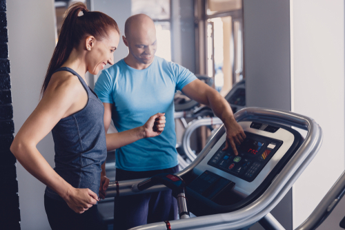 Coach showing woman how to run on treadmill