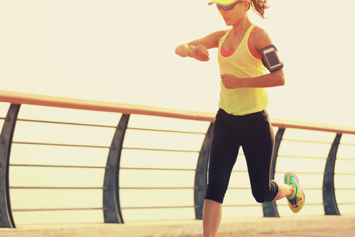 Sporty woman checking watch while running