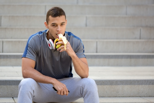 Sporty man eating banana after a walk