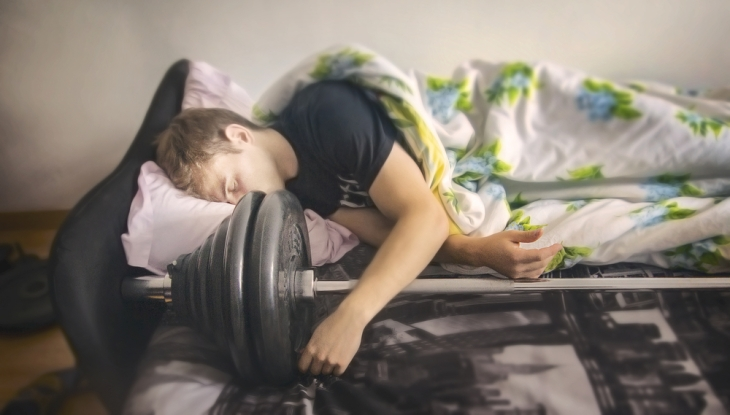 Athlete resting on a barbell - rest concept