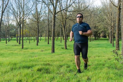 Heavyset man fitness walking in a park