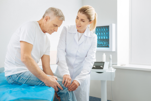 Doctor checking patient's knee