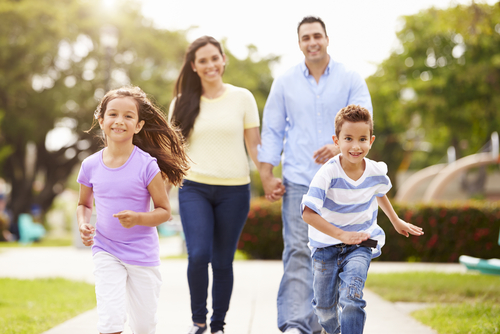 Family with young kids walking together in park