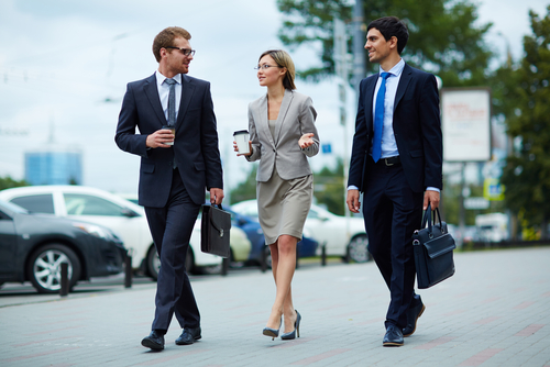 Businesspeople walking and drinking coffee