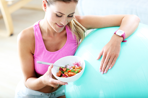 Sporty woman eating a salad after a workout