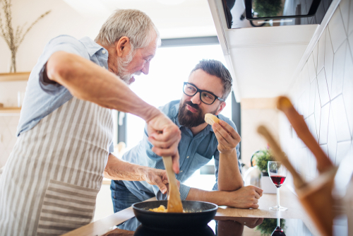 Father and son cooking breakfast together