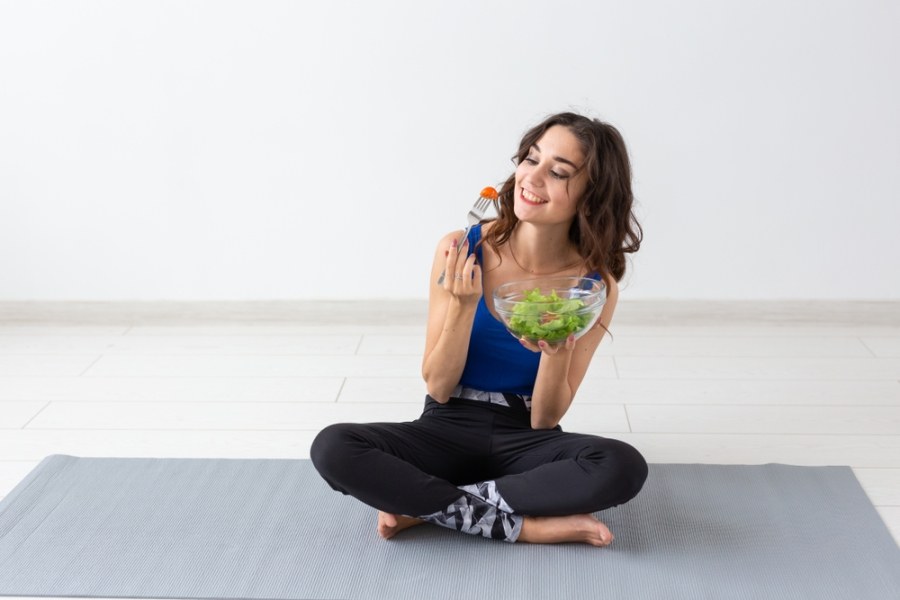 Woman eating a low calorie salad after a workout