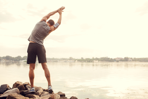 Sporty guy stretching near the water