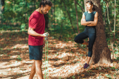 Couple using a resistance band during a walk