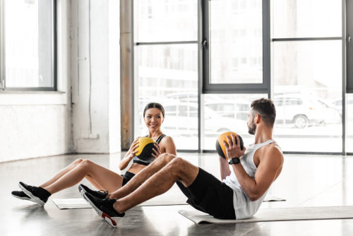 Couple using yoga mat and medicine balls