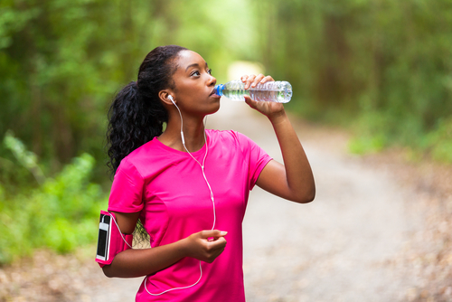 Woman drinking water during a run or walk