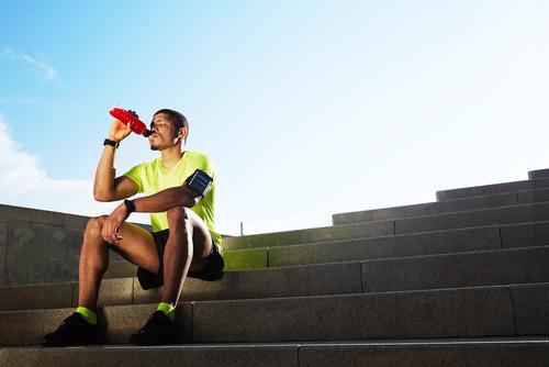 Man drinking a sports drink after a run